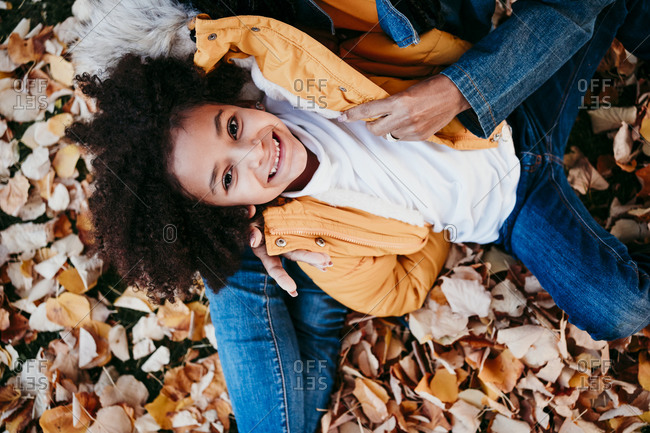 Girl smiling while lying on mother lap at park