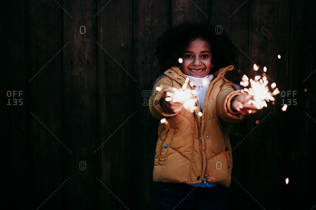 Smiling girl standing and playing with sparkler at night