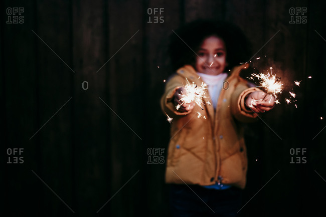 Girl standing and holding burning sparkler at night