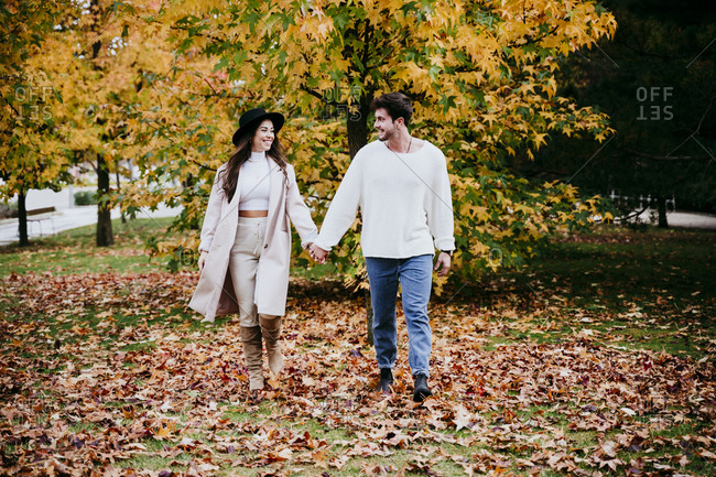 Smiling young couple holding hands while looking at each other against tree during autumn