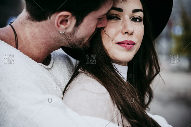 Affectionate man embracing while looking at female partner against sky in city