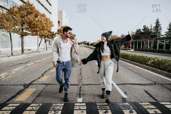 Beautiful smiling woman holding hands with male partner while walking on road in city