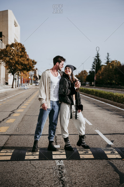 Smiling woman holding hands while looking at male partner on road in city