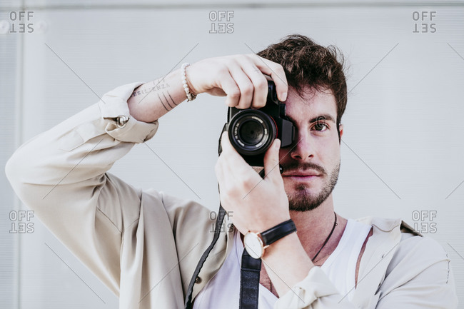 Confident man taking photograph through camera while standing against wall