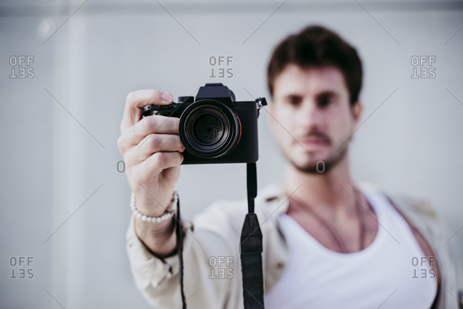 Man taking photograph through camera while standing against wall