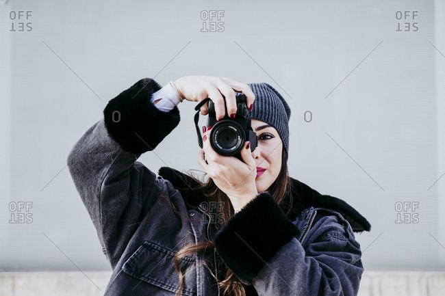 Confident woman taking photograph through camera while standing against wall