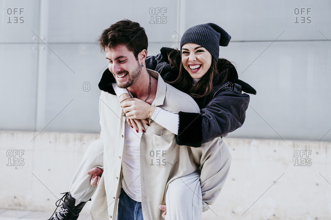 Smiling man piggybacking female partner while standing against wall
