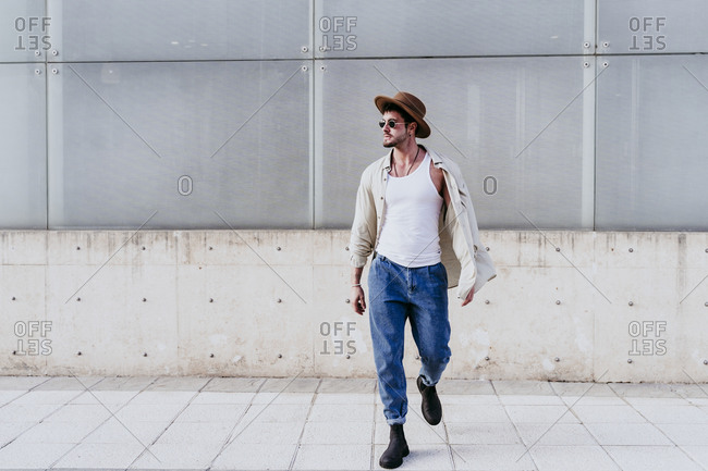 Confident man in hat looking away while walking against wall