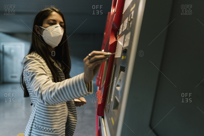 Female passenger with face mask buying ticket from kiosk during COVID-19
