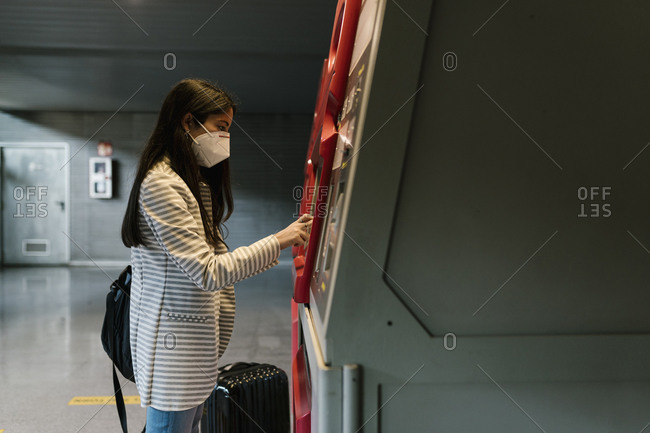 Woman with face mask using kiosk for buying train ticket during COVID-19