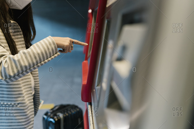 Female passenger buying ticket from kiosk during COVID-19
