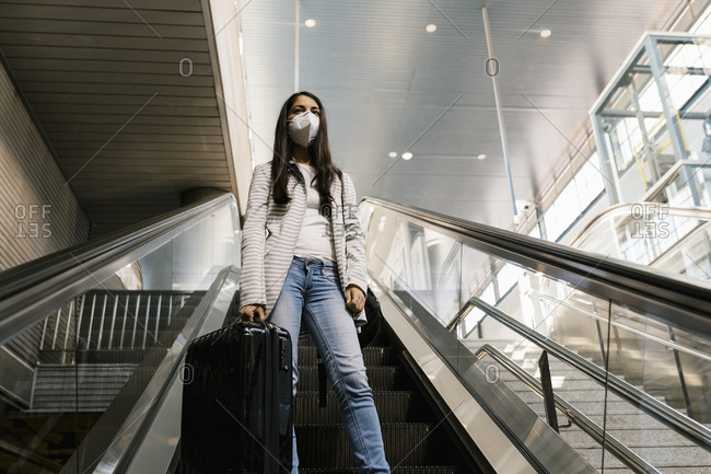 Woman wearing face mask while standing with luggage on escalator at subway station