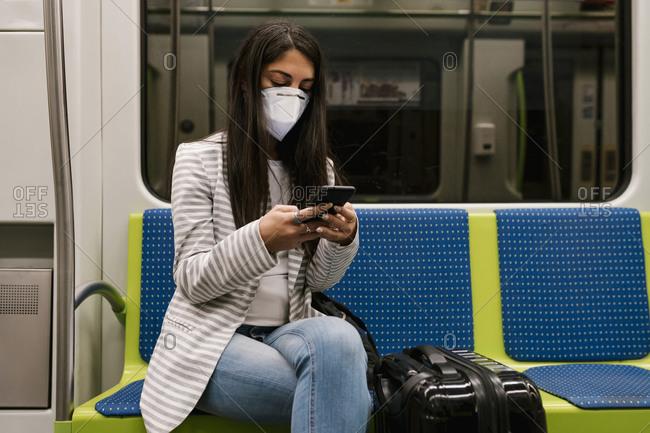 Female passenger using smart phone while sitting in metro train