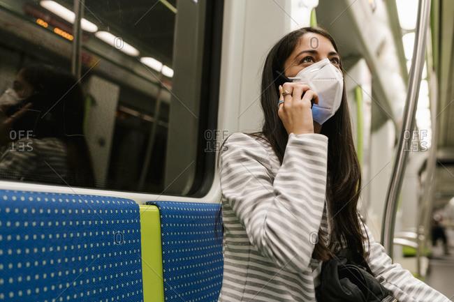 Woman looking away while talking on smart phone in metro train