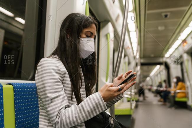 Female passenger text messaging through smart phone in metro train