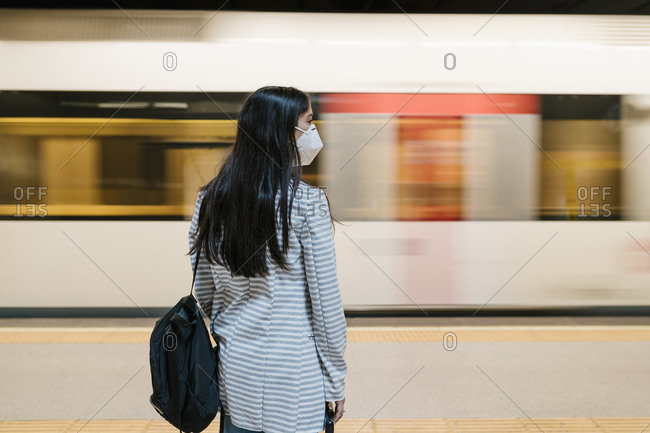 Woman waiting for her train at metro station during pandemic