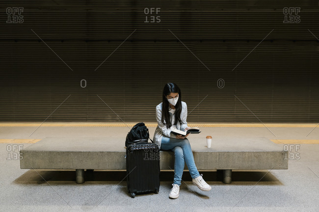 Female passenger reading book while sitting at metro station