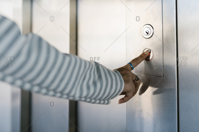 Hand of woman pressing lift button at station