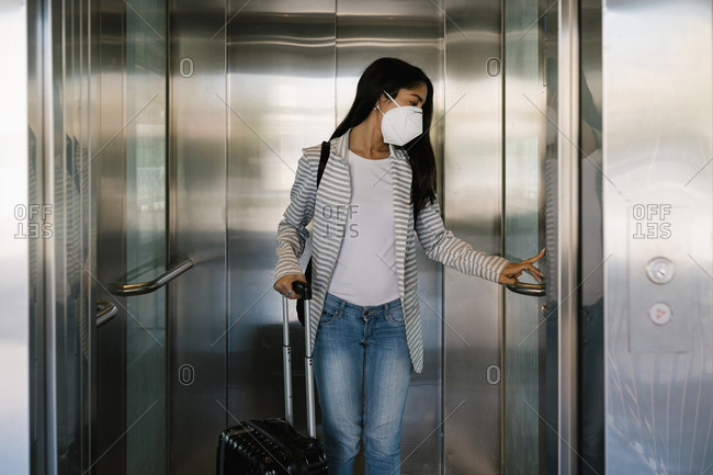 Woman wearing protective face mask pressing elevator button at station