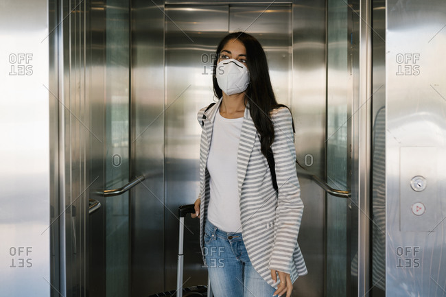 Woman wearing protective face mask walking out with luggage from elevator at station