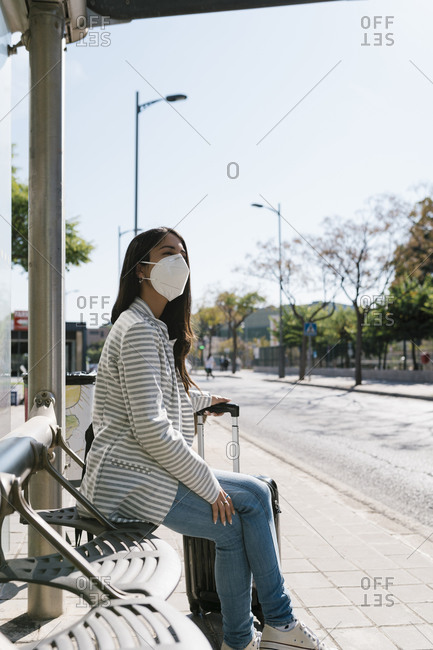 Woman waiting for bus on sunny day during COVID-19 pandemic