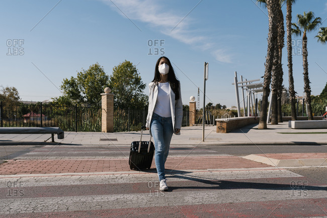 Woman with luggage crossing street against blue sky on sunny day during pandemic