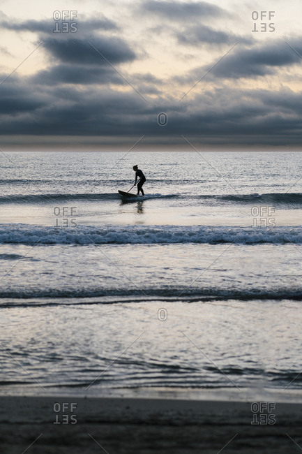 Mature woman paddleboarding on Mediterranean Sea against sky during dawn
