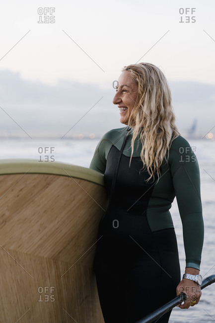 Blond woman laughing while holding paddleboard standing at beach during dawn