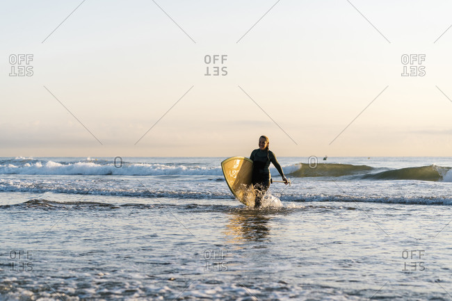 Happy woman walking with paddleboard on Mediterranean Sea at dawn