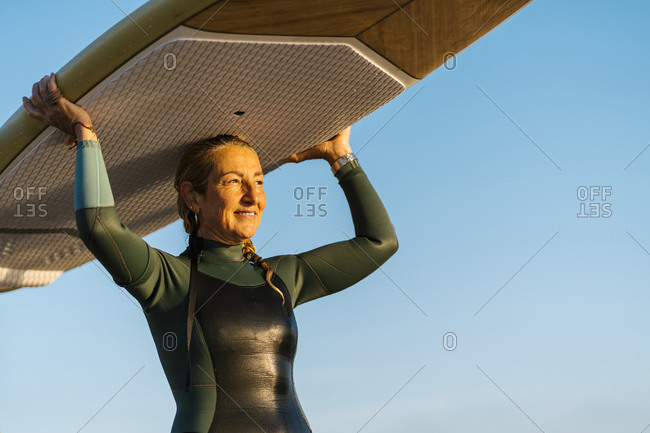 Mature woman carrying paddleboard on head while standing against blue sky