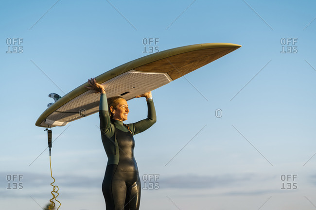 Mature woman looking away while carrying paddleboard on head standing against blue sky