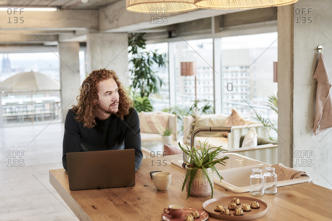 Redhead man looking away while leaning on table at home