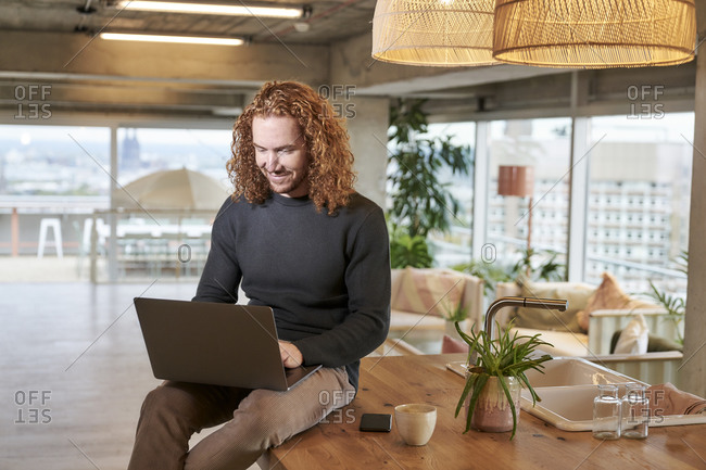 Smiling redhead man using laptop sitting on table at home
