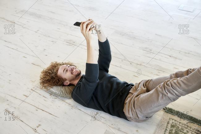 Smiling man taking selfie through smart phone lying down on floor at home