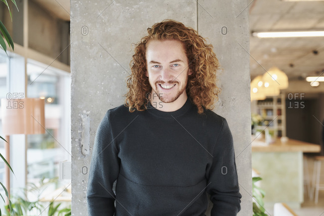 Smiling redhead man standing against column at home