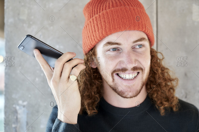 Smiling man listening audio on smart phone while standing against gray column at home