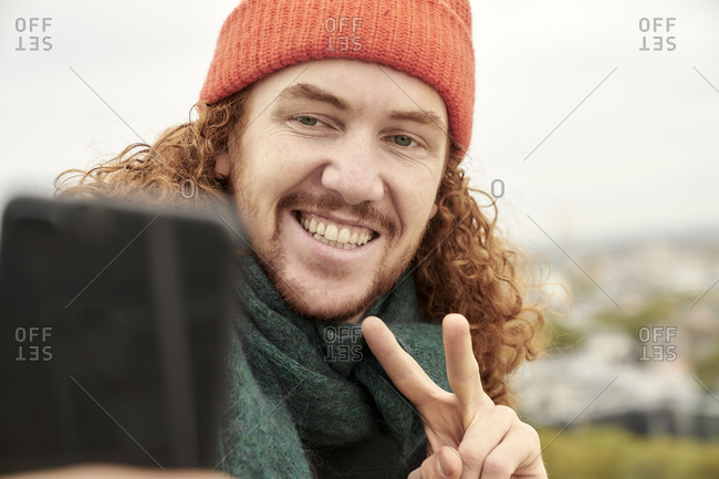 Smiling man doing peace sign while taking selfie on smart phone