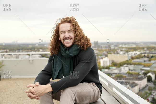 Smiling redhead man sitting on building terrace