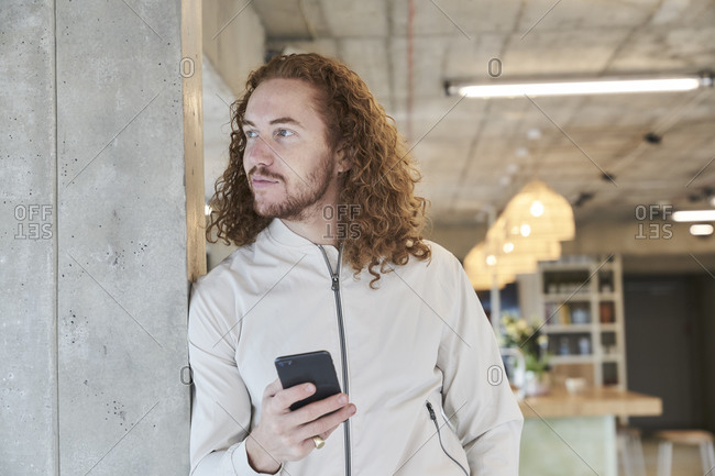 Hipster man looking away while holding smart phone leaning on concrete column at home