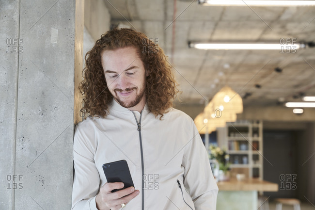 Smiling redhead man using smart phone leaning on column at home