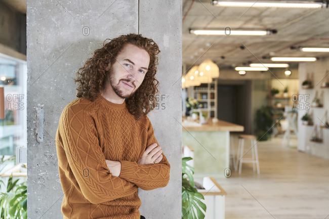 Redhead man with arms crossed standing against concrete column in living room at home