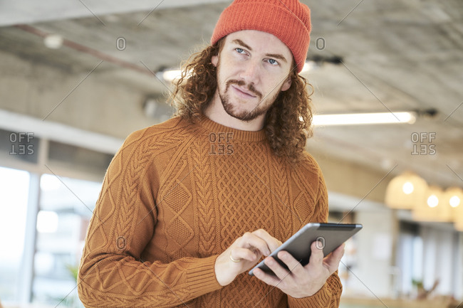 Hipster man using digital tablet looking away while standing in living room at home