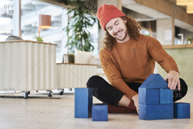 Hipster man playing with toy block while sitting on floor in living room at home