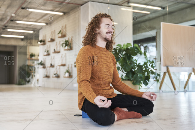Smiling man meditating while sitting on floor in living room at home