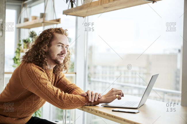 Redhead man using laptop while looking away sitting at home