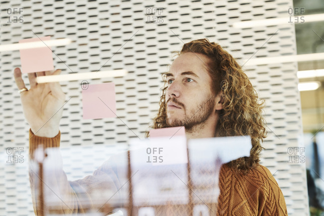 Hipster man sticking sticky notes on glass material at home