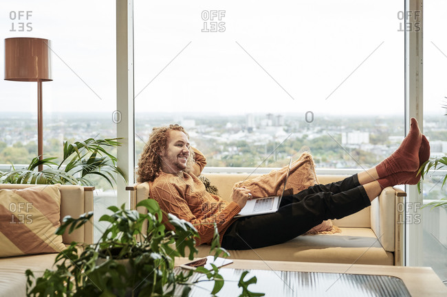 Smiling man using laptop looking away while lying on sofa in living room at home