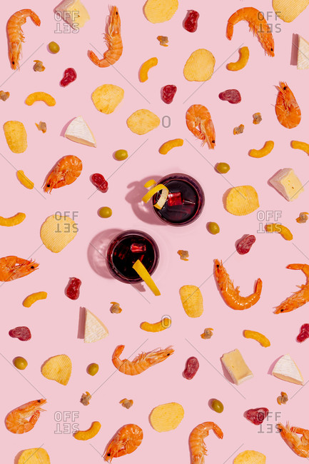 Variation of appetizer with vermouth drink on pink background