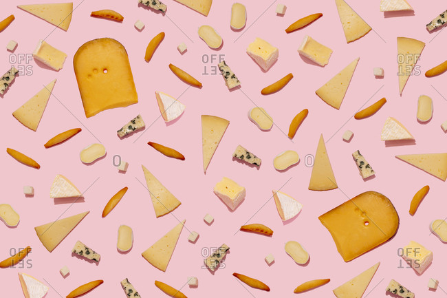 Varieties of cheese and bread sticks on pink background