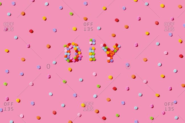 Colorful fluffy pom poms arranged on pink background